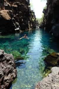 person swimming in the crystal clear waters of Las Grietas Beach