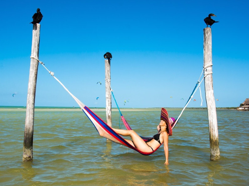 Woman lounging on a hammock set up a few inches above the sea level in Isla Holbox