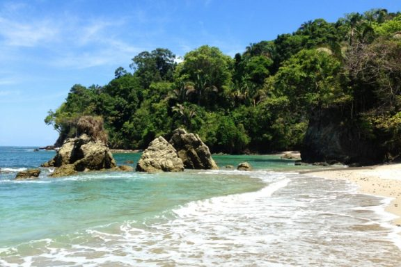 The turquoise waters in Playa Manuel Antonio with luscious forest in the distance