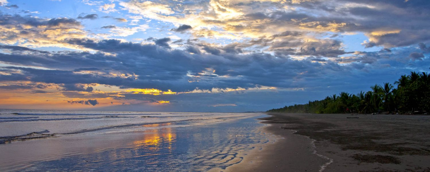 A beautiful sunset is reflected on the sand and water of Playa Las Lajas