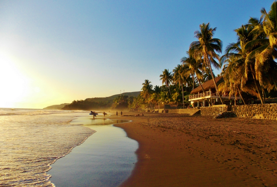 Palm trees line this surfer-friendly black-sand beach at sunset