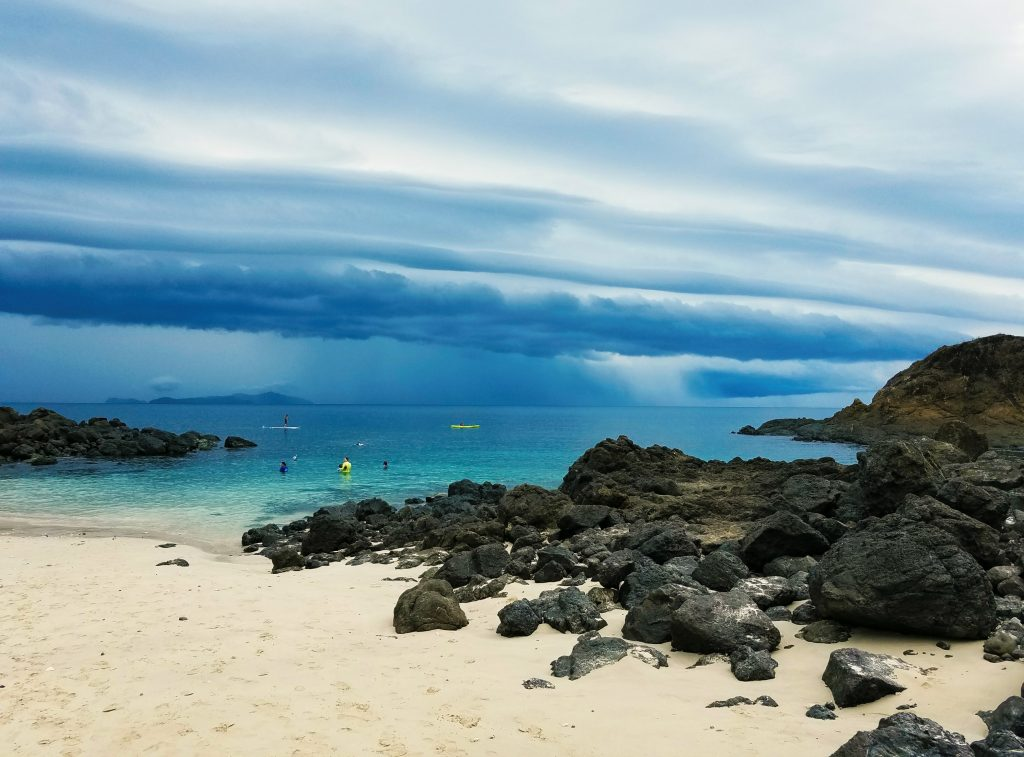 Rainy clouds approach the white-sand beach that's dotted with small rock formations