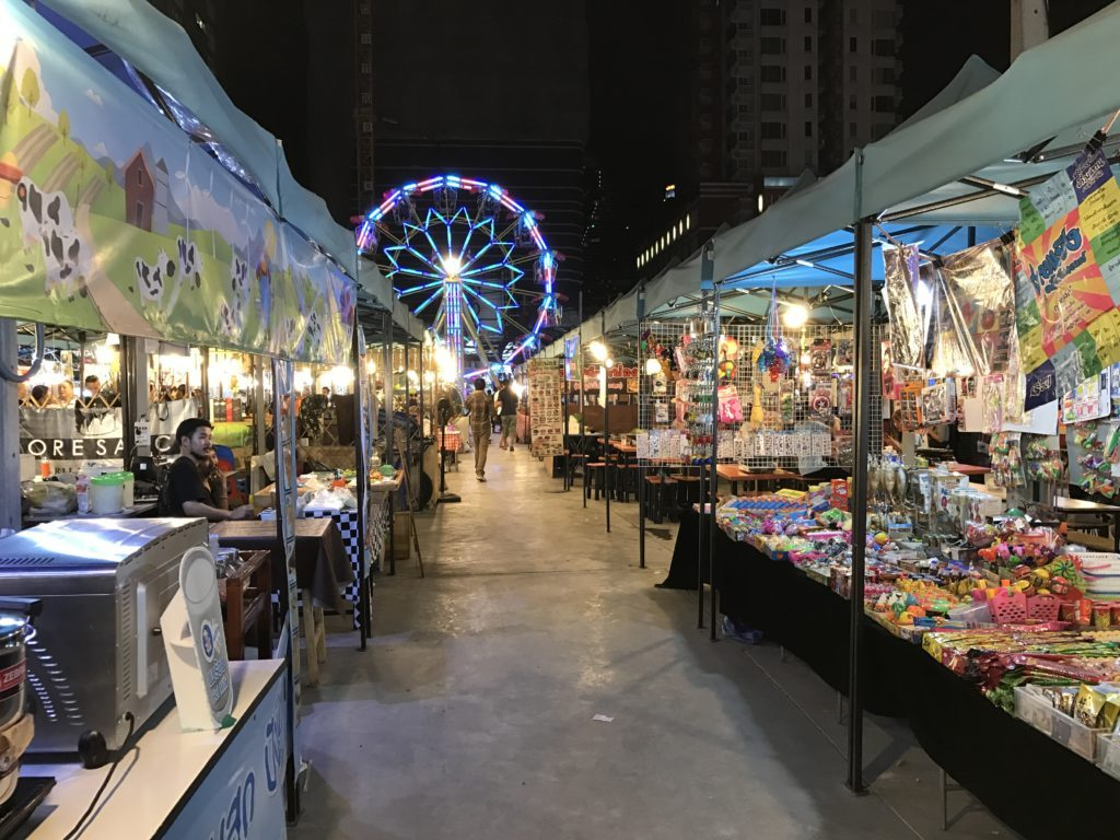 View of vendor stalls and the ferris wheel at Talad Neon Night Market in Thailand