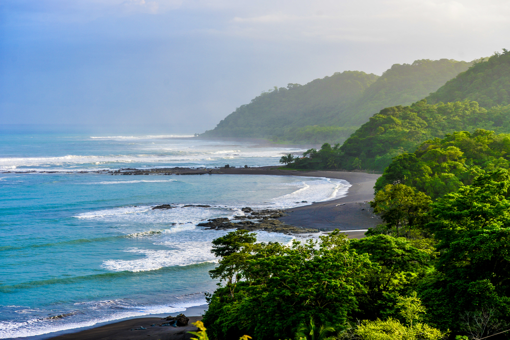 Black sands connect the green-covered mountains to the turquoise crystal-clear ocean waters