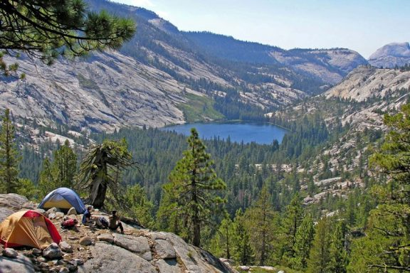 Campers set their tents to spend the night on a high park of the Yosemite National Park overlooking a small lake and a thick forest