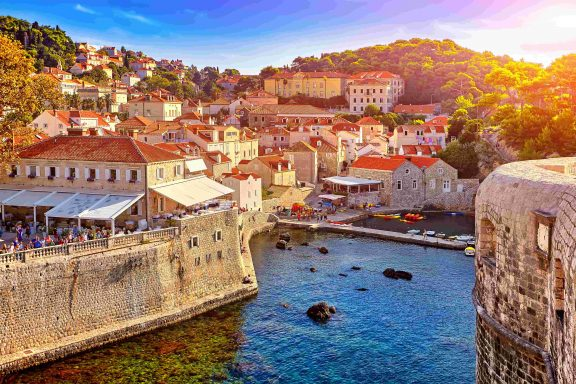 The hot sun shines over Dubrovnik on the place where the sea and the city walls meet