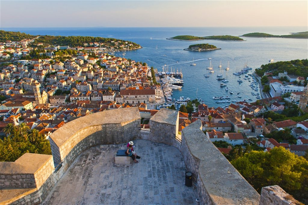 The city of Hvar seen from above on a sunny day during May, with a tourist on the lookout point and the entire town sprawling out underneath