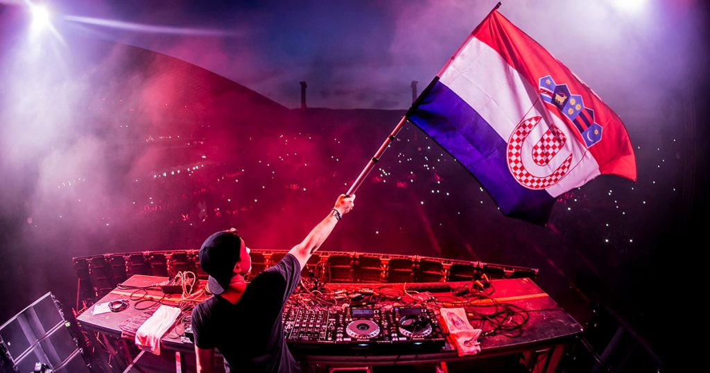 A DJ waves a Croatian flag while entertaining hundreds of thousands of people in the Ultra Europe music festival un July (Jul)