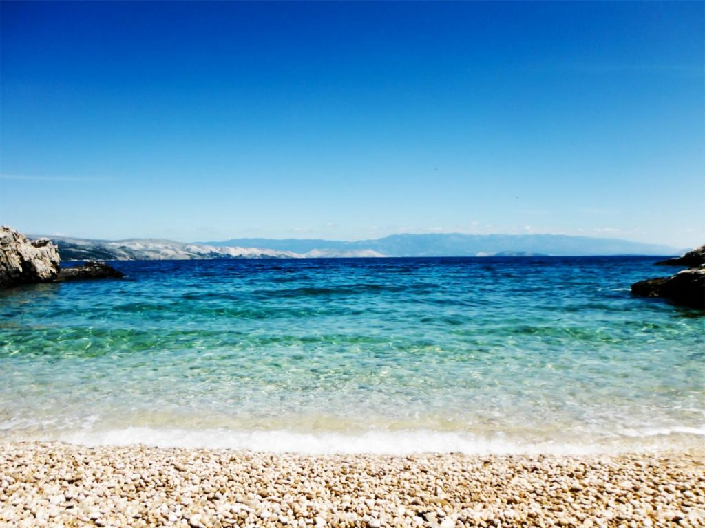 A beach in the Adriatic Coast sprawls out in front of the camera with yellow and brown pebbles on the floor, the crystal-clear turquoise waters of the Adriatic Sea in August (Aug)