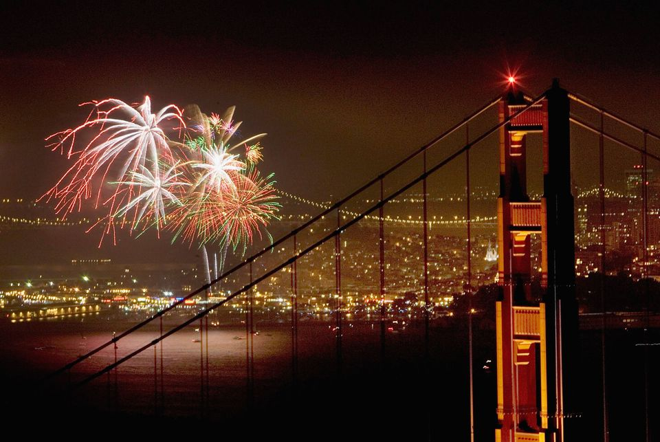 The fireworks on the 4th of July are sent up to the air from behind the Golden Gate Bridge