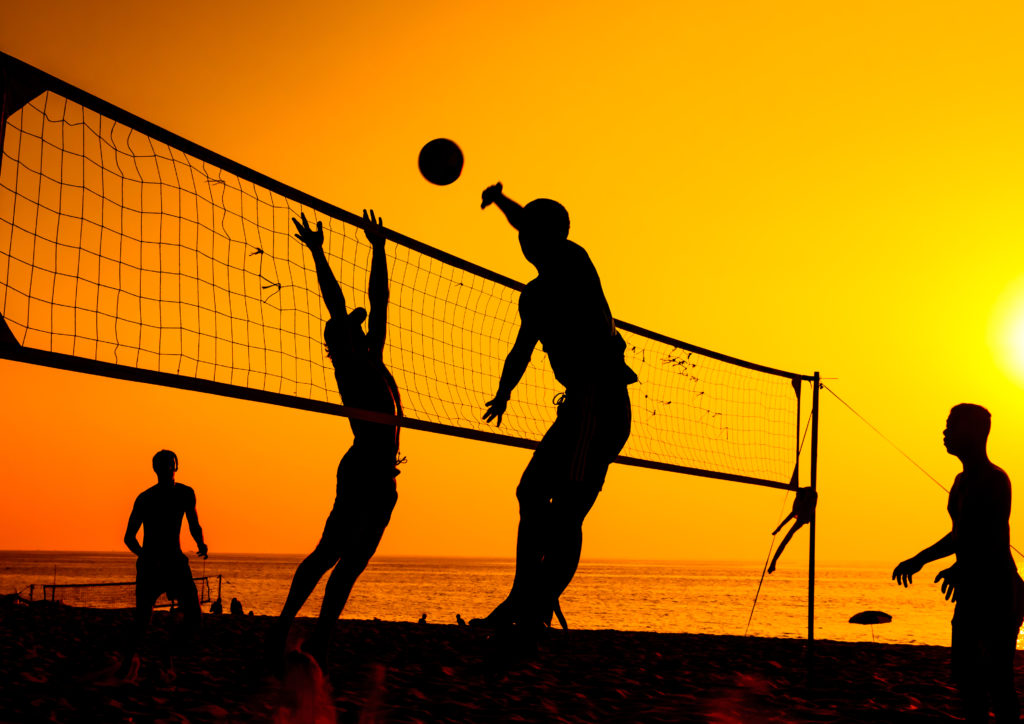 People playing volleyball at sunset on a beach with friends