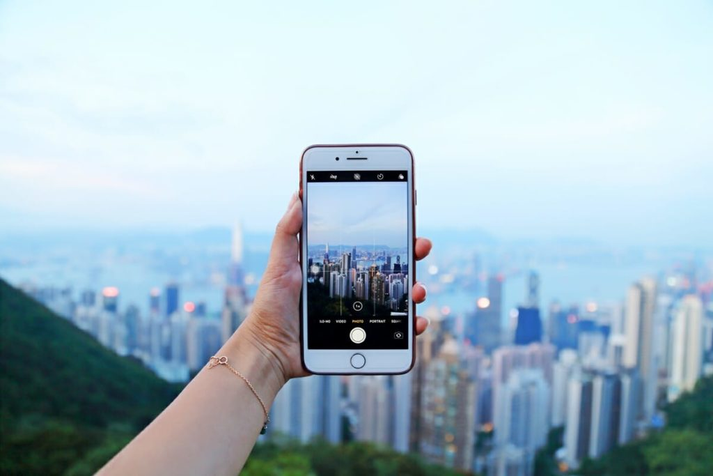 A person holds up an iPhone to take a picture of the skyline of a city at dusk