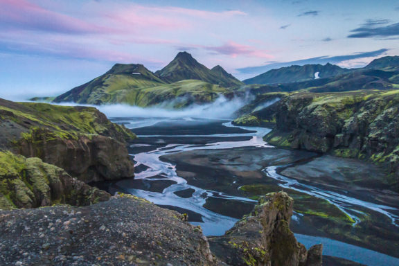 Mountains covered in green and brown with a water stream slowing toward the camera make for the best time to visit Iceland