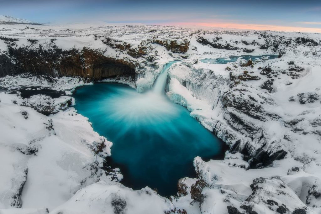 A waterfall flows down into the deep-blue lake surrounded by icy cliffs and snow