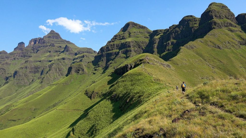 A man hikes through a trail carved out on the Drakensberg Mountains, now covered in green vegetation