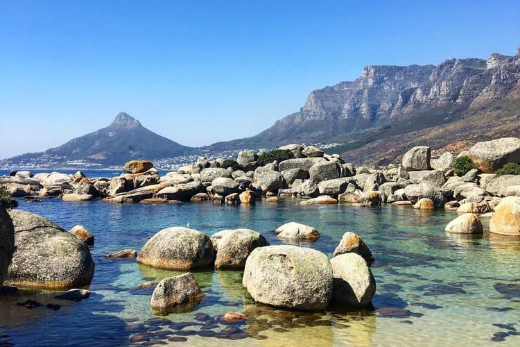 Groups of small rocks pile up on the crystal-clear water of Oudekraal Beach