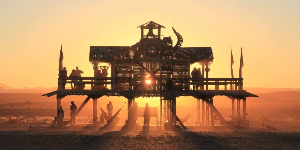 A wooden structure stands in front of the camera with the setting sun behind it