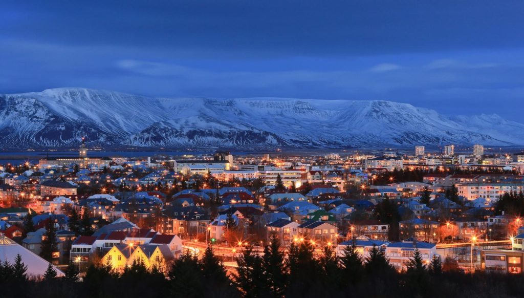 A snow-covered mountain encircles the city of Reykjavik