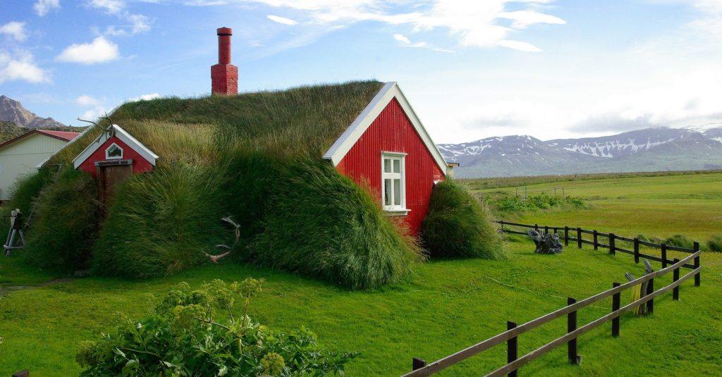 A red house covered in moss and grass characteristic of some Icelandic villages