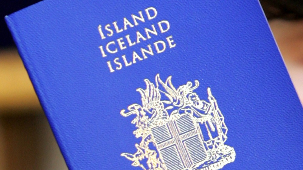A person holds up a passport of Iceland