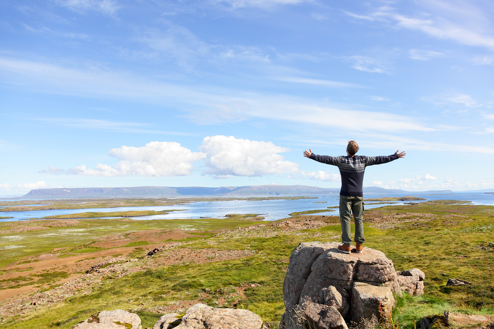 A man stands on a rock with his arms open taking in the fresh air of Iceland