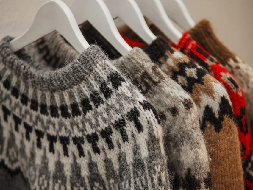 Several hangers displayed side by side holding up Icelandic sweater made from wool